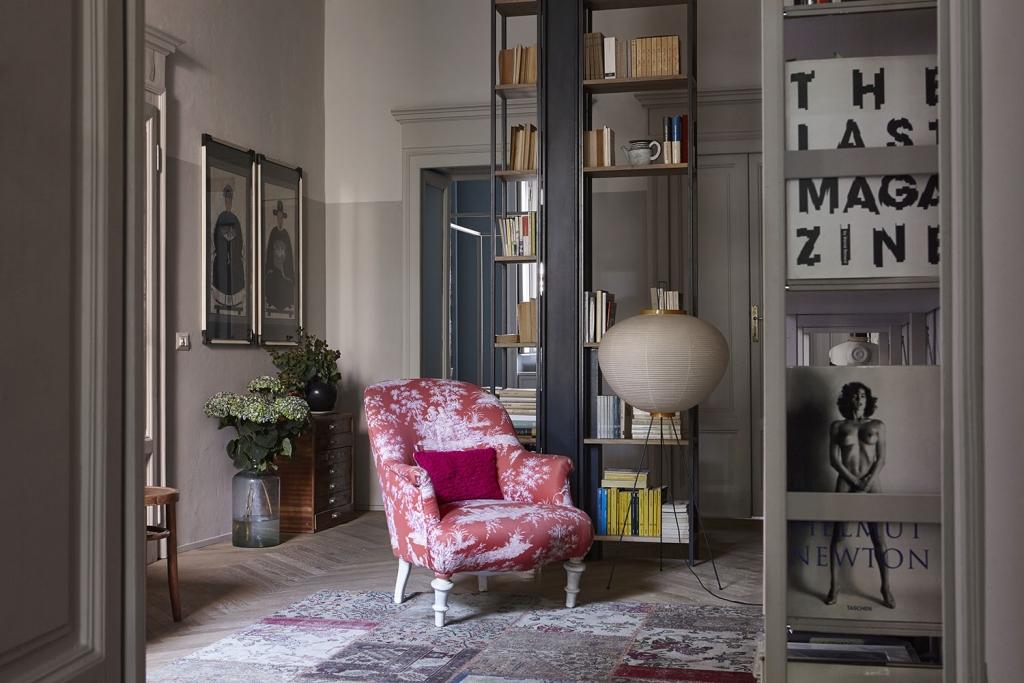 Nel living, sul tappeto Yamamak di Rug Company, poltroncina vintage rivestita con tessuto di Mauel Canovas, cuscino tricot e lino di DesartCasa e lampada Akari 10A, design di Isamu Noguchi per Vitra. Sullo sfondo libreria realizzata su disegno.