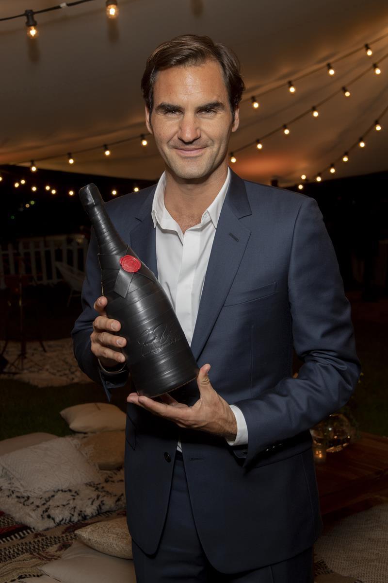 Moët & Chandon Roger Federer Tribute event_Roger Federer posing with 'Greatness Since 1998' magnum bottle