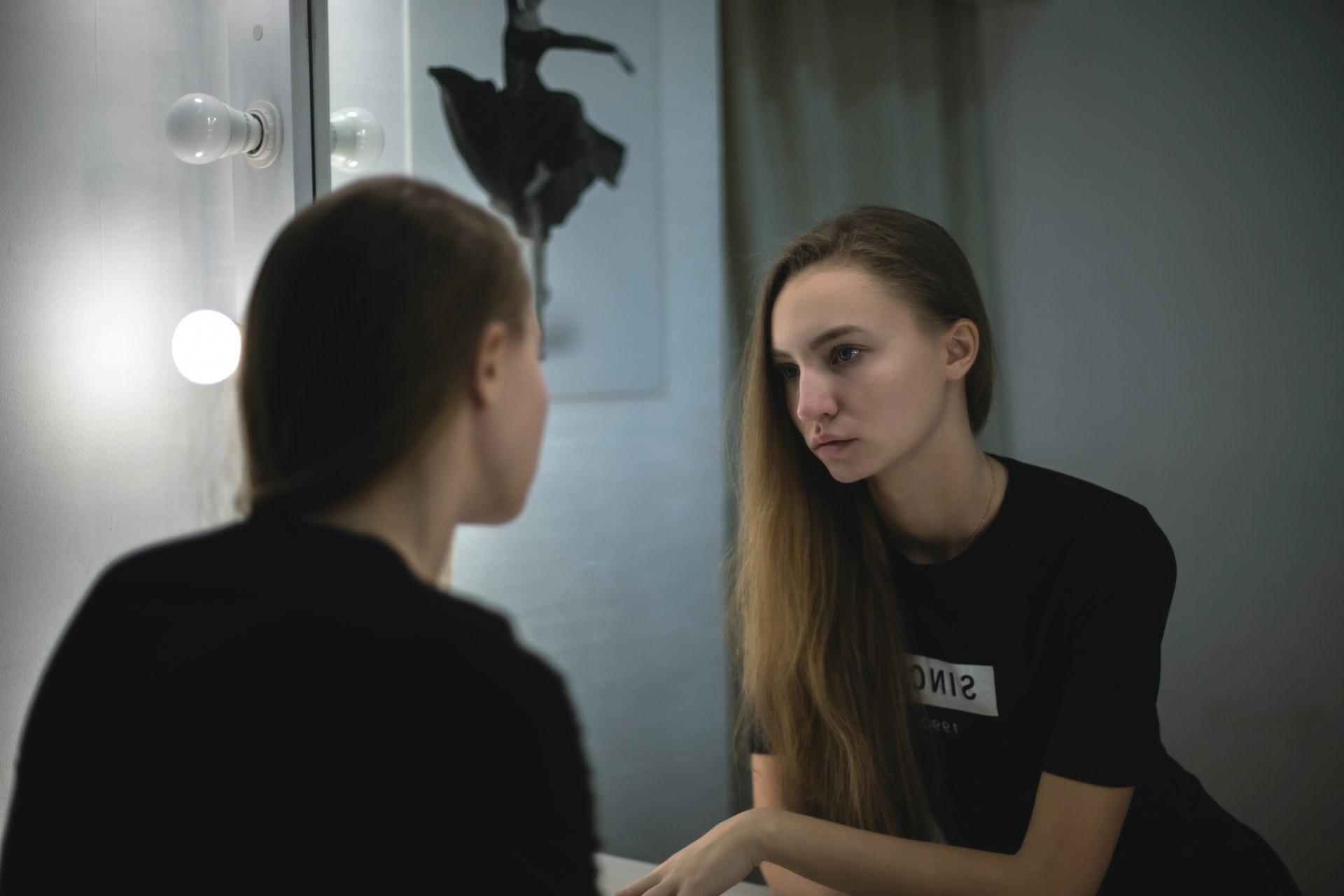 ragazza si guarda allo specchio